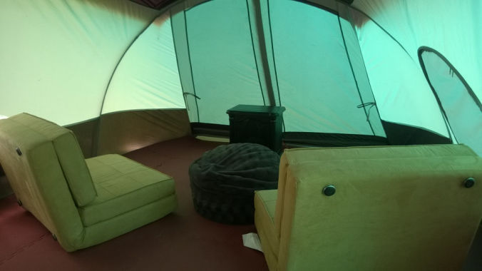 inside of glamping tent showing click back chairs and electric fireplace